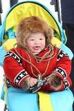 传统毛皮衣物的微笑的男孩Nenets驯鹿牧民 免版税库存照片