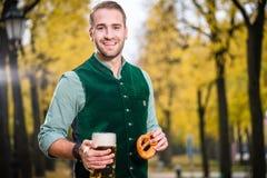 传统巴法力亚Tracht饮用的啤酒的人在巨大的杯子外面 免版税库存照片