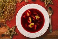 传统波兰圣诞节汤-红色罗宋汤汤用在白色板材的饺子 免版税库存照片