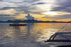从传统渔船的一个看法有舷外架的在Coron海岛盐水湖多云日落的 免版税库存照片