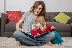 读传说的妈妈和小孩在家预定 图库摄影