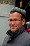 传统盖帽微笑的维吾尔人 库存照片