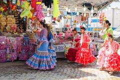 传统礼服的女孩公平地走在塞维利亚的 库存照片
