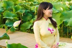 传统礼服的美丽的女孩充当莲花庭院 库存图片