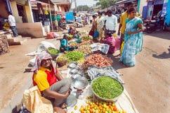 传统礼服的顾客买新鲜的绿豆,土豆,红萝卜的在印地安街道市场上  库存图片
