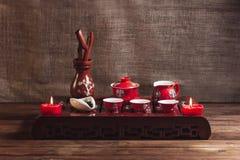 传统红色中国茶具,有traditioanl中国剧院面具的红色瓷 免版税库存图片