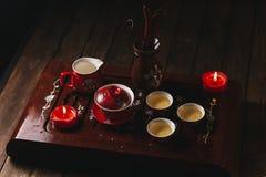 传统红色中国茶具,有traditioanl中国剧院面具的红色瓷 免版税库存照片