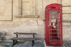 传统红色电话起动和长木凳 免版税库存照片