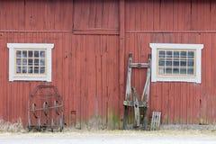 传统红色谷仓墙壁、窗口和雪撬 库存照片