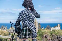 传统苏格兰吹风笛者用在Dunnottar城堡的礼服代码 库存图片