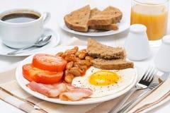 传统英式早餐用煎蛋、烟肉和豆 免版税图库摄影