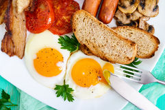传统英式早餐:烟肉,蘑菇,鸡蛋,蕃茄,香肠,豆,在一块白色板材的多士 库存照片