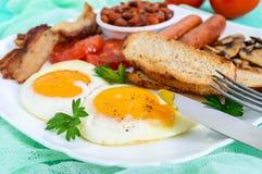 传统英式早餐:烟肉,蘑菇,鸡蛋,蕃茄,香肠,豆,在一块白色板材的多士 免版税图库摄影