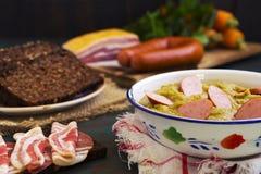 传统荷兰浓豌豆汤和成份在一张土气桌上 免版税库存照片