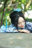 传统蓝色和白色Hanfu礼服攀登的中国妇女在石桌 免版税库存照片