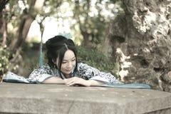 传统蓝色和白色Hanfu礼服攀登的中国妇女在石桌 免版税库存图片