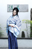 传统蓝色和白色Hanfu礼服的中国妇女在盆景旁边坐 免版税库存照片