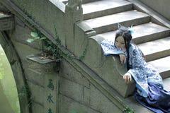 传统蓝色和白色Hanfu礼服的,戏剧亚裔中国妇女在一个著名庭院里 免版税库存照片