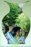 传统蓝色和白色Hanfu礼服的,戏剧在一个著名庭院里,在窗口前面的立场亚裔中国妇女 图库摄影