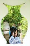 传统蓝色和白色Hanfu礼服的,戏剧在一个著名庭院里,在窗口前面的立场亚裔中国妇女 库存图片