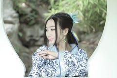 传统蓝色和白色Hanfu礼服的,戏剧在一个著名庭院里,在窗口前面的立场亚裔中国妇女 库存照片