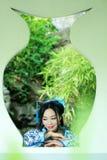 传统蓝色和白色Hanfu礼服的,戏剧在一个著名庭院里,在窗口前面的立场亚裔中国妇女 免版税图库摄影