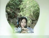 传统蓝色和白色Hanfu礼服的,戏剧在一个著名庭院里,在窗口前面的立场亚裔中国妇女 免版税库存图片