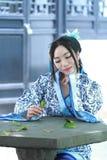 传统蓝色和白色Hanfu礼服的,杀害时间亚裔中国妇女在一个著名庭院里 库存图片