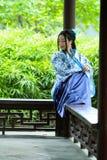 传统蓝色和白色Hanfu礼服的,杀害时间Aisan中国妇女在一个著名庭院里 库存图片
