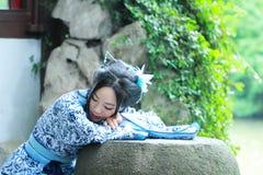 传统蓝色和白色Hanfu礼服的,杀害时间Aisan中国妇女在一个著名庭院里 免版税库存图片