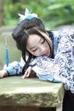传统蓝色和白色Hanfu礼服的,杀害时间Aisan中国妇女在一个著名庭院里 免版税库存照片