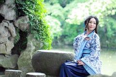 传统蓝色和白色Hanfu礼服的,杀害时间Aisan中国妇女在一个著名庭院里 图库摄影