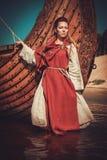 传统衣裳的北欧海盗妇女临近drakkar 免版税库存照片