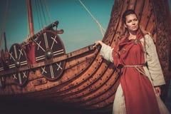 传统衣裳的北欧海盗妇女临近drakkar 图库摄影