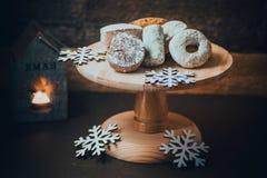 传统西班牙圣诞节曲奇饼polvorones、nevaditos和mantecados在木蛋糕站立,与灼烧的蜡烛 免版税库存照片