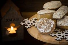 传统西班牙圣诞节曲奇饼polvorones、nevaditos和mantecados在木蛋糕站立,点燃蜡烛, 免版税库存照片