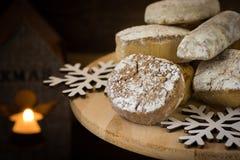 传统西班牙圣诞节曲奇饼polvorones、nevaditos和mantecados在木蛋糕站立,点燃蜡烛, 库存照片