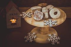 传统西班牙圣诞节曲奇饼polvorones、nevaditos和mantecados在木蛋糕站立,点燃蜡烛 免版税库存照片