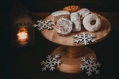传统西班牙圣诞节曲奇饼polvorones、nevaditos和mantecados在木蛋糕站立,烧蜡烛 免版税库存图片