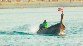 传统长尾巴木汽船在镇静蓝色海驾驶在海滩附近 免版税库存图片