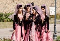 传统面纱的年轻美丽的妇女谈闲话在娱乐事件前 库存照片