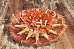 传统食家在老被风化的破裂的木庭院表上的开胃菜美味盘集合 图库摄影