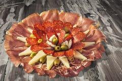 传统食家在老被风化的破裂的木庭院表上的开胃菜美味盘集合 库存图片