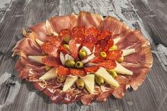 传统食家在老被风化的破裂的木庭院表上的开胃菜美味盘集合 库存照片