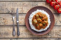 传统马都拉斯黄油牛肉辣调味汁慢厨师羊羔食物用米和蕃茄在黏土盘 库存照片