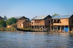 传统高跷房子和长的小船在水u中 免版税库存照片