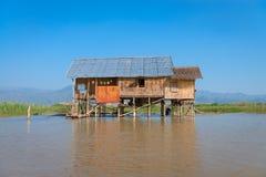 传统高跷房子在水中在蓝天下 免版税库存照片