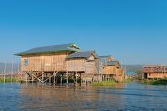 传统高跷房子在水中在蓝天下 图库摄影