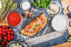 传统calzone意大利薄饼用西红柿酱、无盐干酪和蒜味咸腊肠 免版税库存图片