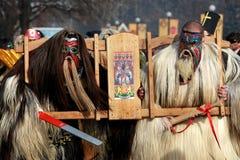 传统Kukeri服装的未认出的人被看见在化妆舞会比赛Kukerlandia的节日在扬博尔,保加利亚 免版税库存照片